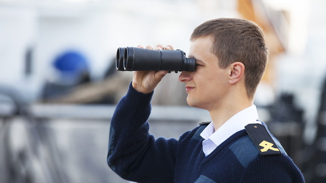 Man with binoculars (refer to: Mar­itime Se­cu­ri­ty)